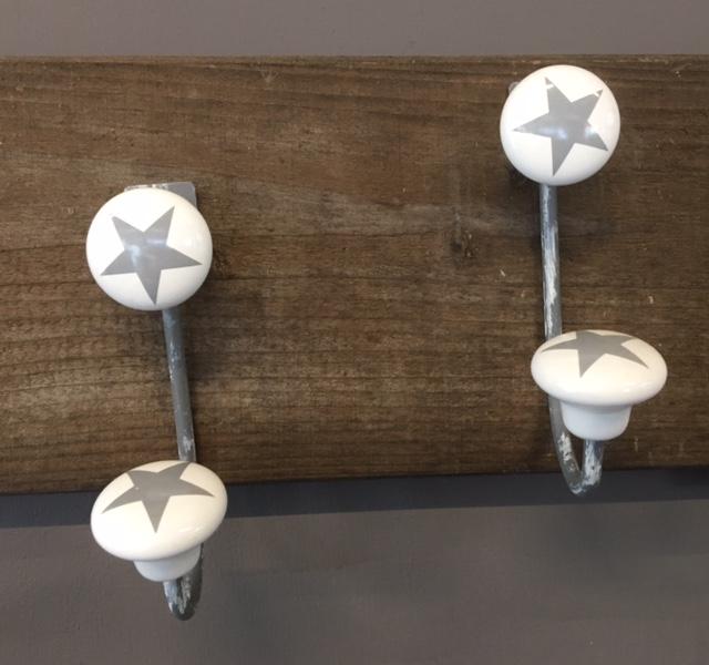 Metalen (old-look) kapstok haak met keramiek witte knoppen met grijze ster op afgebeeld.